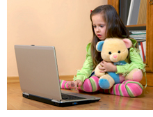 Photo of girl holding her stuffed animal while playing on a laptop computer
