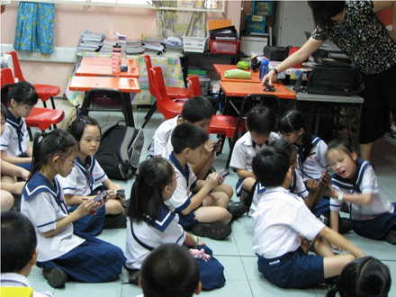 Photo of 3rd grade students  from Singapore using mobile computers in a conversational manner